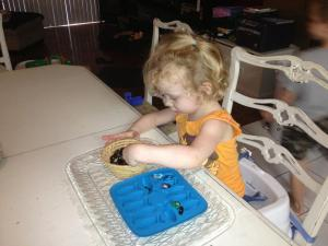 Ella Scooping Gems into a fish tray